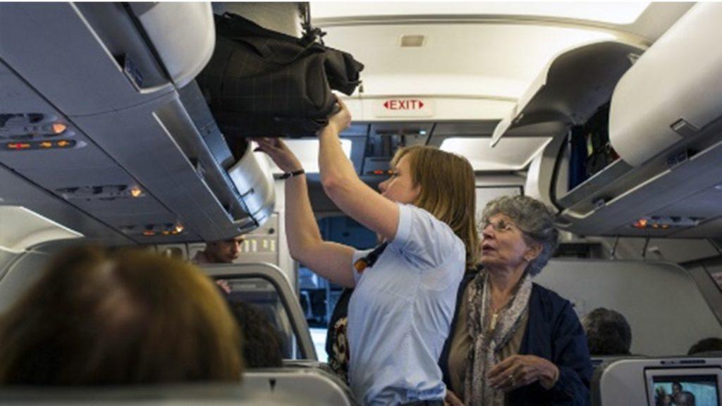 Перекладывание ручного багажа в специально отведенное место на борту самолета АЗУР Эйр
